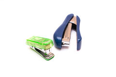 Small and Large Plastic Staplers. A small green stapler with a large blue stapler on a white background royalty free stock images
