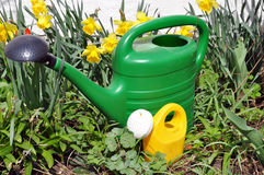 Small and large Watering-Can. Two watering cans, a small one and a large one. Could be used to symbolize child and parent royalty free stock images