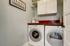 Small laundry room with door and washr dryer set. Small laudnry room with tile floor, door, and washer dryer set stock photos
