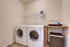 Small laundry room with white appliances and wicker basket. Has tile floor Stock Image