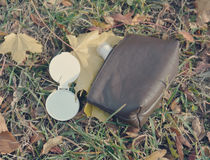 Small leather purse lying on the ground with mirror and conseale Royalty Free Stock Photography