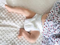 The legs of a newborn in a diaper stock images
