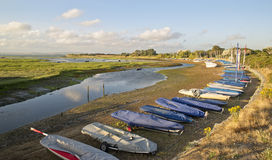 Small leisure boats moored at low tide in marina at Summer sunse Royalty Free Stock Image