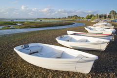 Small leisure boats moored at low tide in marina at Summer sunse Stock Images
