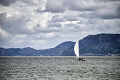Small leisure sailing boat on Menai Straits in Anglesey Wales wi. Small leisure sailing boat on Menai Straits in Anglesey Wales landscape Royalty Free Stock Image