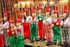 Small liars. A bunch of small Pinocchio figures on a market in Florence Stock Image