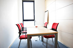 Small light empty office room with table and red chairs Royalty Free
