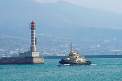 Small lighthouse. The towboat passs by a beacon on the end of a pier Stock Images
