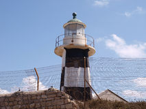 Small Lighthouse Behind Barbed Wires Stock Image