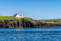 Red and white lighthouse on cliff with village in a distance – view from sea royalty free stock photo
