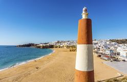 Small lighthouse next to Fishermen Beach in Albufeira, Algarve,. Wide, almost empty beach along cliffs viewed from Miradouro do Pau da Bandeira, Albufeira Stock Image