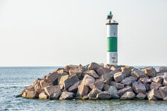Small lighthouse on a pile of rocks at Lake Michigan Stock Images