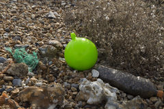 Small lime green sea buoy. And home made ballast weight resting on a shingle beach Stock Images