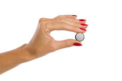 Small lithium battery. Close up of woman's hand with red nails holding a small shiny lithium battery. Studio shot isolated on white Royalty Free Stock Photography