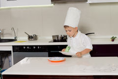 Small little boy in a chefs uniform wiping dishes Royalty Free Stock Photos