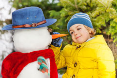 Small little boy put carrot making snowman Royalty Free Stock Images