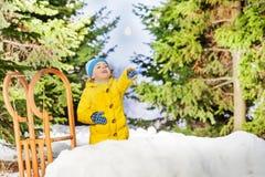 Small little boy throw snowball in park Stock Photos