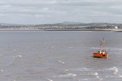 A small little fishing boat is rocked by the waves and windy weather in Morecambe Bay - Winter 2019 royalty free stock photo