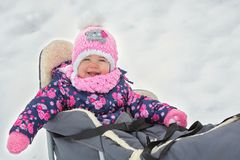 Small little girl sitting on her sledge Royalty Free Stock Photos