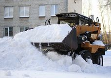 Small loader rakes fallen snow. A small loader rakes the fallen white snow on a bright Sunny winter March day Stock Images