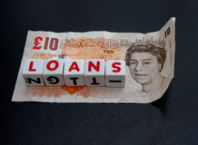 Small loans. A ten pound note with text ' loans ' in red uppercase text on small white cubes , dark background Stock Photo