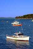 Small Lobster Fishing Boat in Maine Coast Bay. Small lobster fishing boat at port in a scenic calm bay on the picturesque coast of Maine Royalty Free Stock Photo