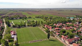 Small local amateur football pitch located at town suburbs. Surrounded by residential houses and fields stock video