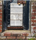 Small locked gate in a brick wall Stock Photo