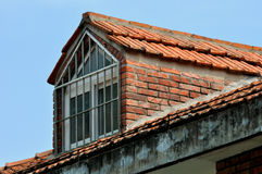 Small loft window on the top of building. Made by red brick and tile, under blue sky, shown as interesting shape and color contrast Stock Photography