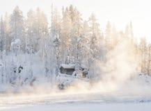 Small log cabin behind vaporing river Royalty Free Stock Photos