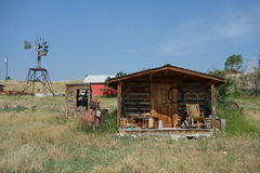 A small log cabin with a windmill in idaho Stock Image
