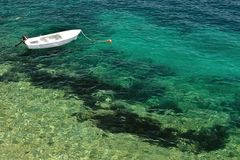 Small lonely fishing boat floating alone on adriatic sea stock photography