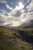 Small lonely hiker standing in enormous cloud and sunlight covered autumn wilderness Stock Photography
