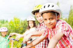 Small looking African boy in helmet with friends Royalty Free Stock Photography