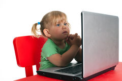 Small looking on the laptop young girl Royalty Free Stock Photos