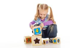 The small lovely girl collects toy cubes. Royalty Free Stock Photo