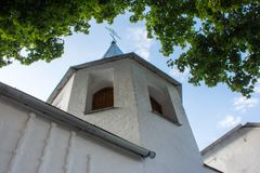 Small and low bell tower near the church with bricks, painted white, with an Orthodox Christian cross on top on blue sky backgroun Royalty Free Stock Image