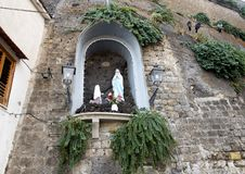 Small Madonna and Child statues, Marina Grande, Sorrento. Pictured is a small statue of the Madonna and worshipper in an alcove on a narrow street in Marina Stock Image