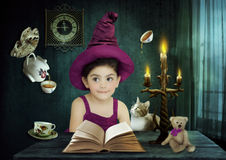 Small magician. Little girl in the hat magician, sitting at a table in front of an open book, deals with the magic of by night in the room by candlelight Stock Photography