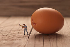 Small man breaks an egg. The concept of cooking Stock Photo