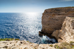 Small man Giant Cliffs - Migra l-Ferha, Malta, Europe. Waves smash against massive cliffs, towering above the blue mediterranean sea, dwarfing a lone figure Stock Image