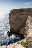 Small man Giant Cliffs - Migra l-Ferha, Malta, Europe. Waves smash against massive cliffs, towering above the blue mediterranean sea, dwarfing a lone figure Royalty Free Stock Images