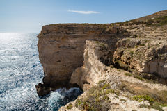 Small man Giant Cliffs - Migra l-Ferha, Malta, Europe. Waves smash against massive cliffs, towering above the blue mediterranean sea, dwarfing a lone figure Royalty Free Stock Photo