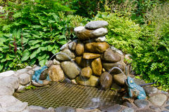 A small man-made water fountain with rocks and artificial frogs near the Capilano Suspension Bridge area in Vancouver, Canada.  Stock Photo