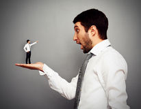 Small man pointing at the amazed big man. Concept photo over dark background Royalty Free Stock Photo