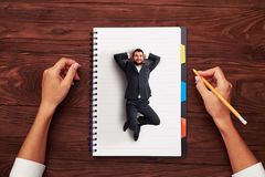 Small man resting on big notepad Royalty Free Stock Photos