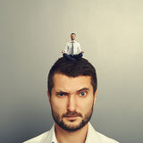 Small man sitting on the head big man Royalty Free Stock Photography