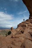 Small man standing in hole of arches national park stock photo