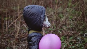 A small man stands in a jacket, in a gas mask and with a ball in his hand. Looks like a dwarf or a child. There was a chemical attack stock footage