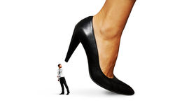 Small man under big heel Stock Photography